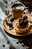 Cupcake with caramel cream and blackberry, served with coffee