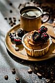 Cupcake mit Karamellcreme und Brombeeren dazu eine Tasse Kaffee