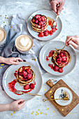 Pancakes with strawberries and honey for a family breakfast with coffee