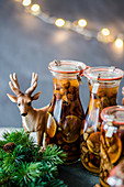 Homemade Christmas liqueur with dried fruits, citrus and nuts