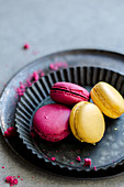 Raspberry and lemon macaroons served on a black tray