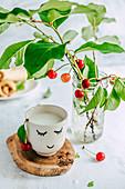 Milk in a smiling mug, fresh cherry