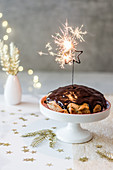New Year's cake with chocolate glaze, asterisk cold sparkles, golden additions