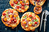 Mini pizza with caramelized onion, mozzarella and tomatoes
