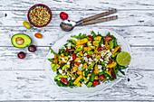 Fruity salad plate with arugula, tomatoes, mango, avocado, roasted pine nuts and feta