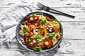 Spaghetti mit gebratenen Zucchinischeiben, Tomaten, Feta und Basilikum
