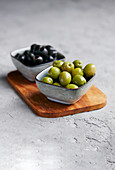 Green and black olives in small bowls