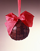 A chocolate ball with a red bow