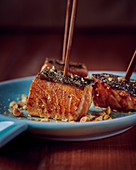 Salmon cubes with coffee crust, ginger, thyme honey and peanuts