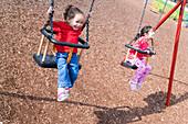 Young girls swinging on playground swings