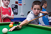 Child learning to play pool