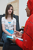 Social worker interviewing sulky teenager