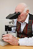 Elderly man looking through microscope