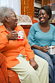 Daughter and mother having a laugh over a cup of tea