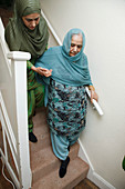South Asian woman helping her mother on stairs