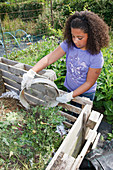 Girl putting weeds into compost heap