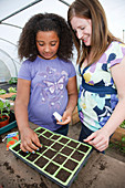 Woman with daughter planting seeds in a tray