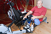 Man with prosthetic limb using a rowing machine at the gym