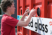 Teenaged boy recycling glass at bottle bank at city tip