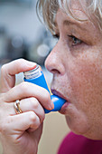 Middle aged woman with asthma using an inhaler