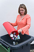 Woman putting tins and cans into recycling wheelie bin