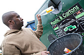 Man putting plastic bottle into recycling bank