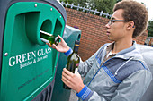 Teenage boy putting bottles into a recycling bank