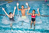 Group of children splashing around in swimming pool