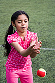 Young girl trying to catch a tennis ball