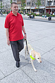 Vision impaired man with guide dog