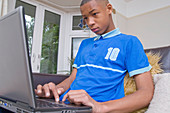 Teenaged boy working on a laptop computer at home