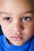 Upset young boy with tears streaming down his face