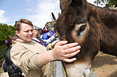 Young woman with learning disabilities stroking a donkey