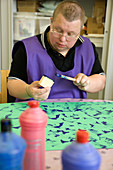 Man with learning disabilities using sponge shapes to paint