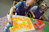 People with learning disabilities using sponges to paint