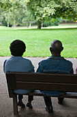 Couple of older people sitting on a bench in the park