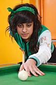 Girl playing pool in youth club
