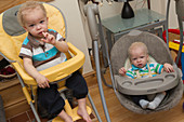 Boys at home in baby chairs