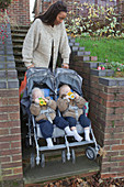 Mother going up steps with twins in buggy