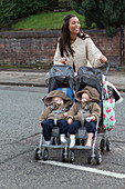 Mother crossing road with twins in buggy