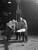 Three workers handle a red hot billet, 1963