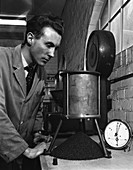 A lab technician undertaking a coal flow test, 1962