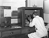 Lab technician with microscope at a steelworks, 1962
