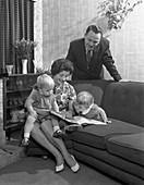 Family group looking at a brochure, 1963