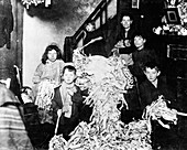 Making party streamers at home, London, c1900