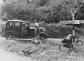 People relaxing by a signpost with a 1935 Standard, Devon