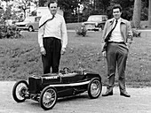 Two men standing by a miniature Sunbeam pedal car, 1960s
