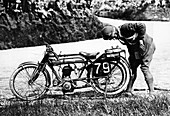 Norman Black repairing a puncture on his Norton bike, 1920