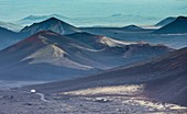 Truck dwarfed by volcanic ranges, Kamchatka, Russia