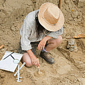 Archaeologist excavating a coin
